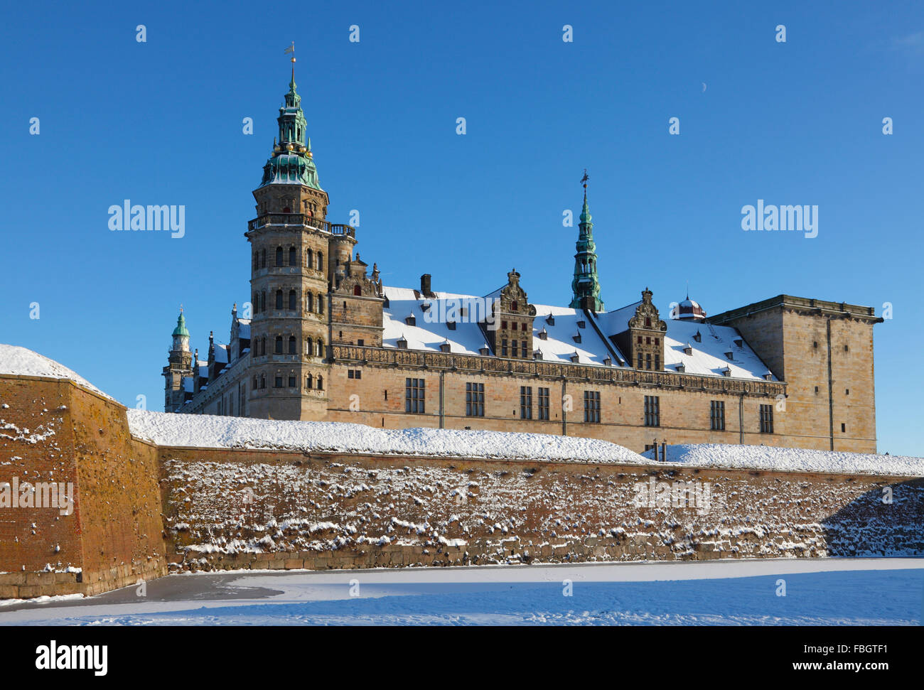 The snow-covered Kronborg Castle in Elsinore, Helsingør, on a sunny winter's day, frozen moat and a blue sky. Stock Photo