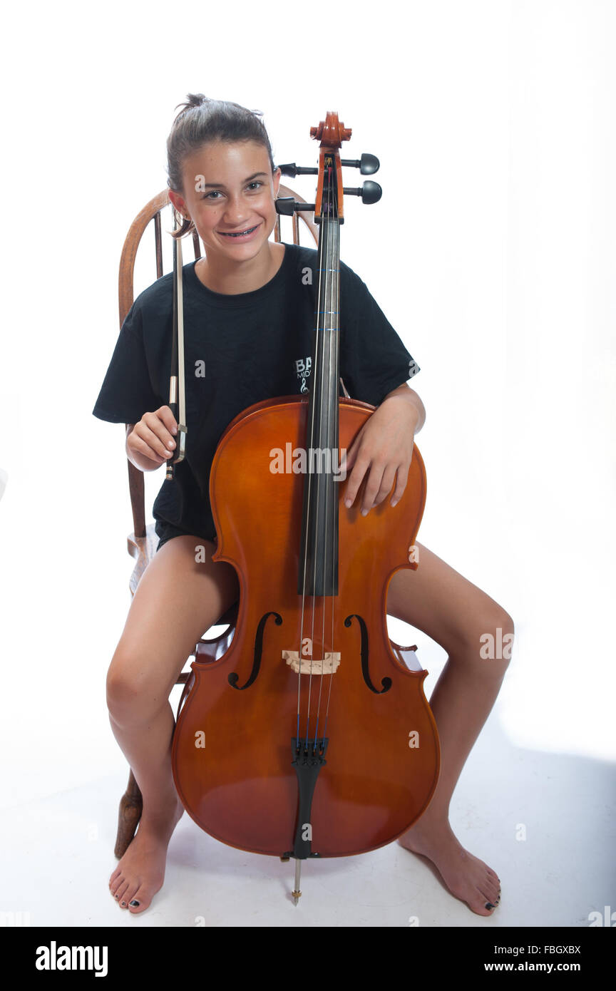 Pre teen girl wide view resting with cello bow on her shoulder. - Stock Image