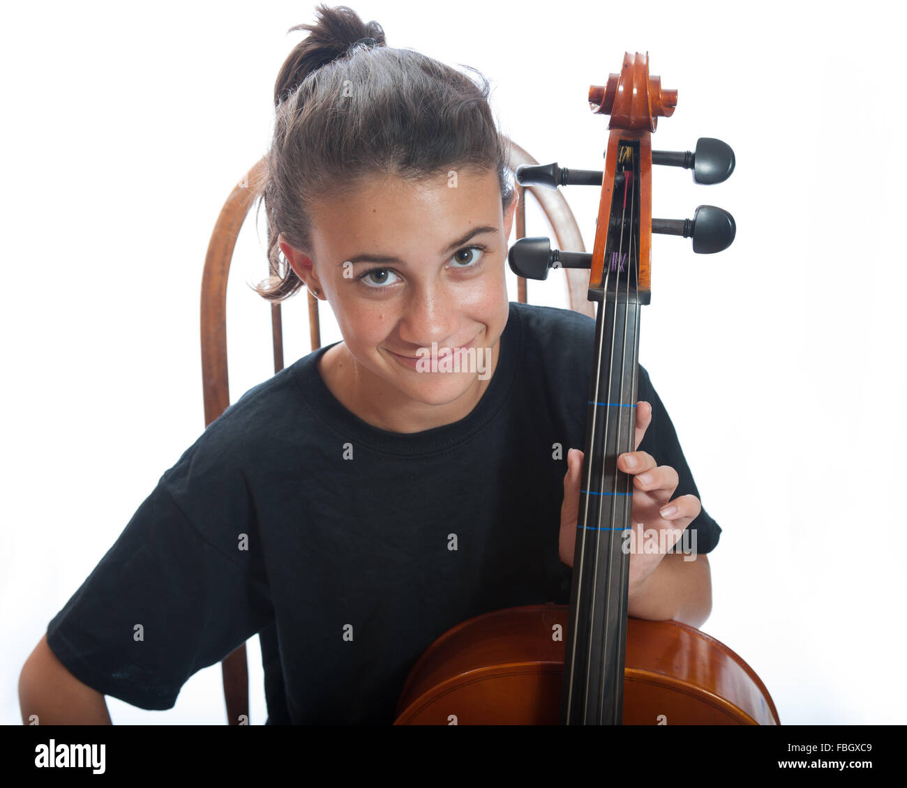 Pre teen girl close view looking up from her cello. - Stock Image