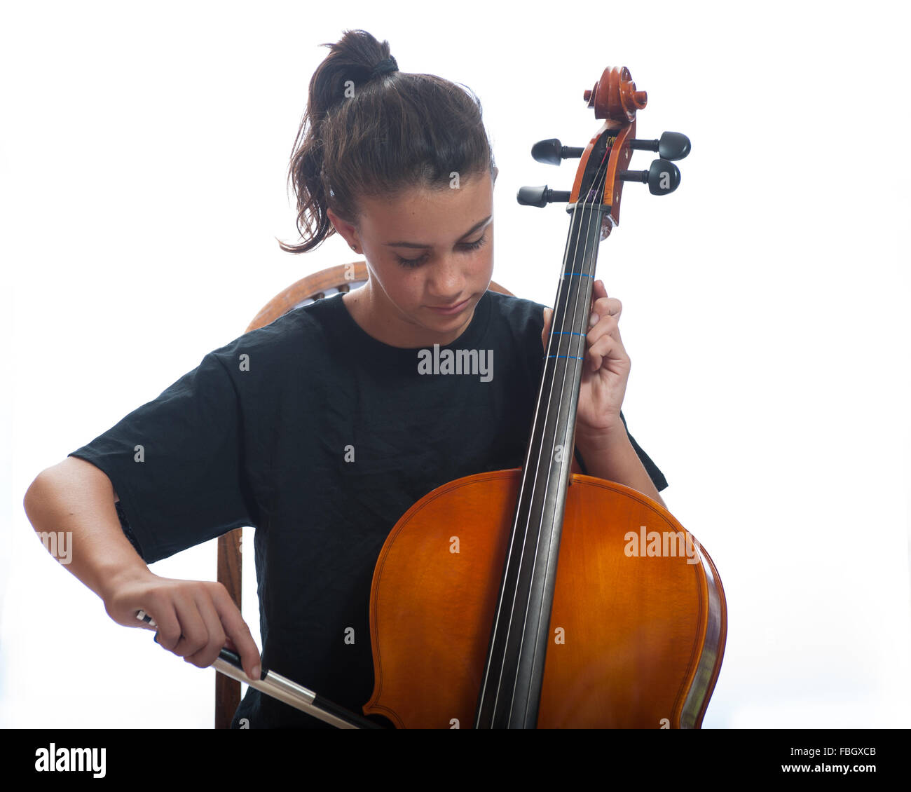 Pre teen girl close up playing her cello. - Stock Image