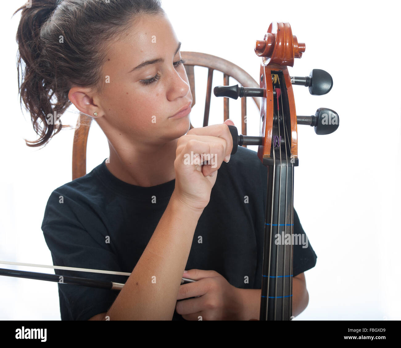 Pre teen girl close up tuning her cello. - Stock Image