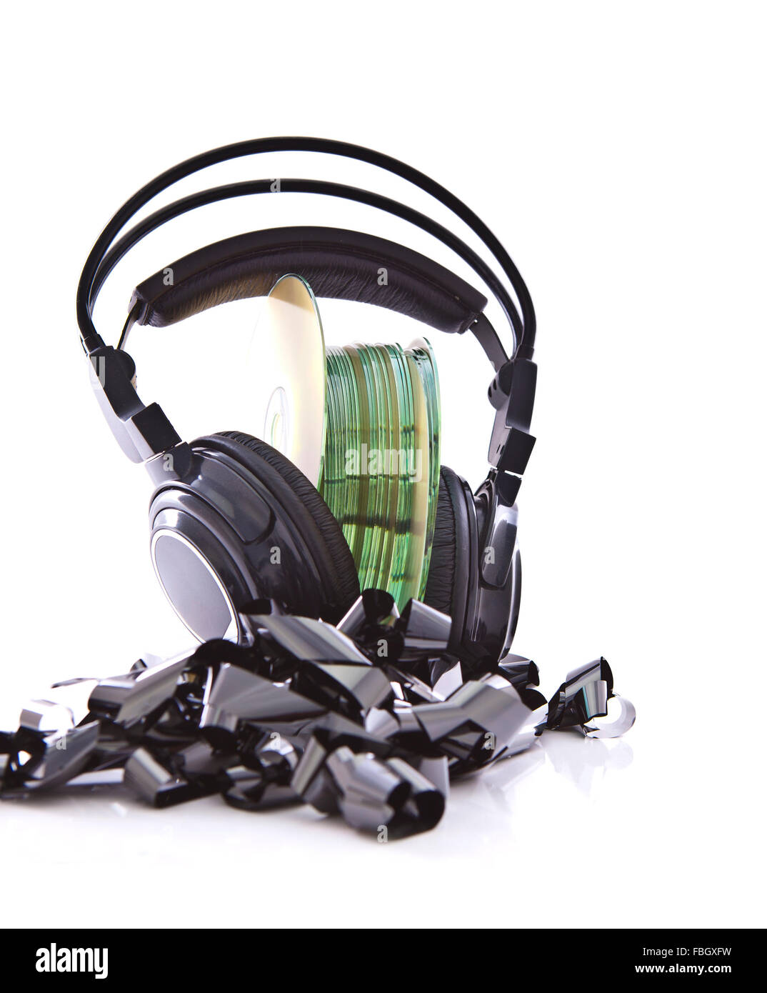 Stack of CDs with HI-Fi headphones on vintage reel of audio tape on white background - Stock Image