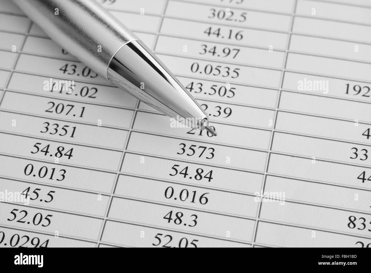 Financial statements. Ballpoint pen on financial statements. Black and white image. Close up. - Stock Image