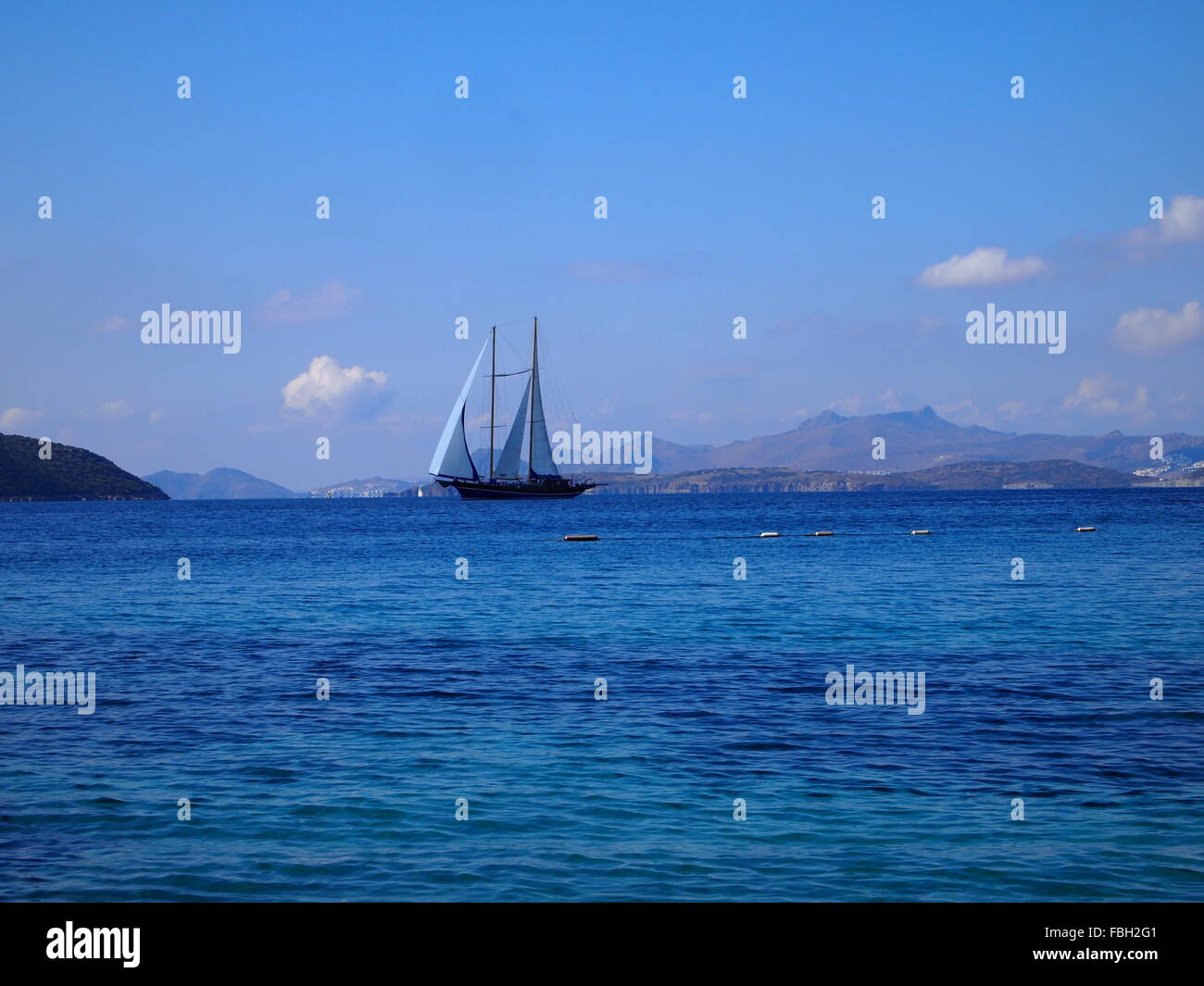 Gulet boat in the distance with blue sky background with a few white clouds and distant land. - Stock Image