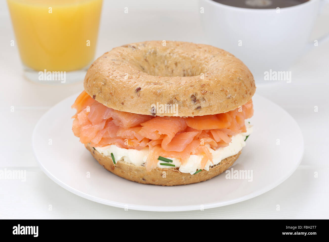 Bagel sandwich for breakfast with salmon fish, cream cheese, orange juice and coffee - Stock Image