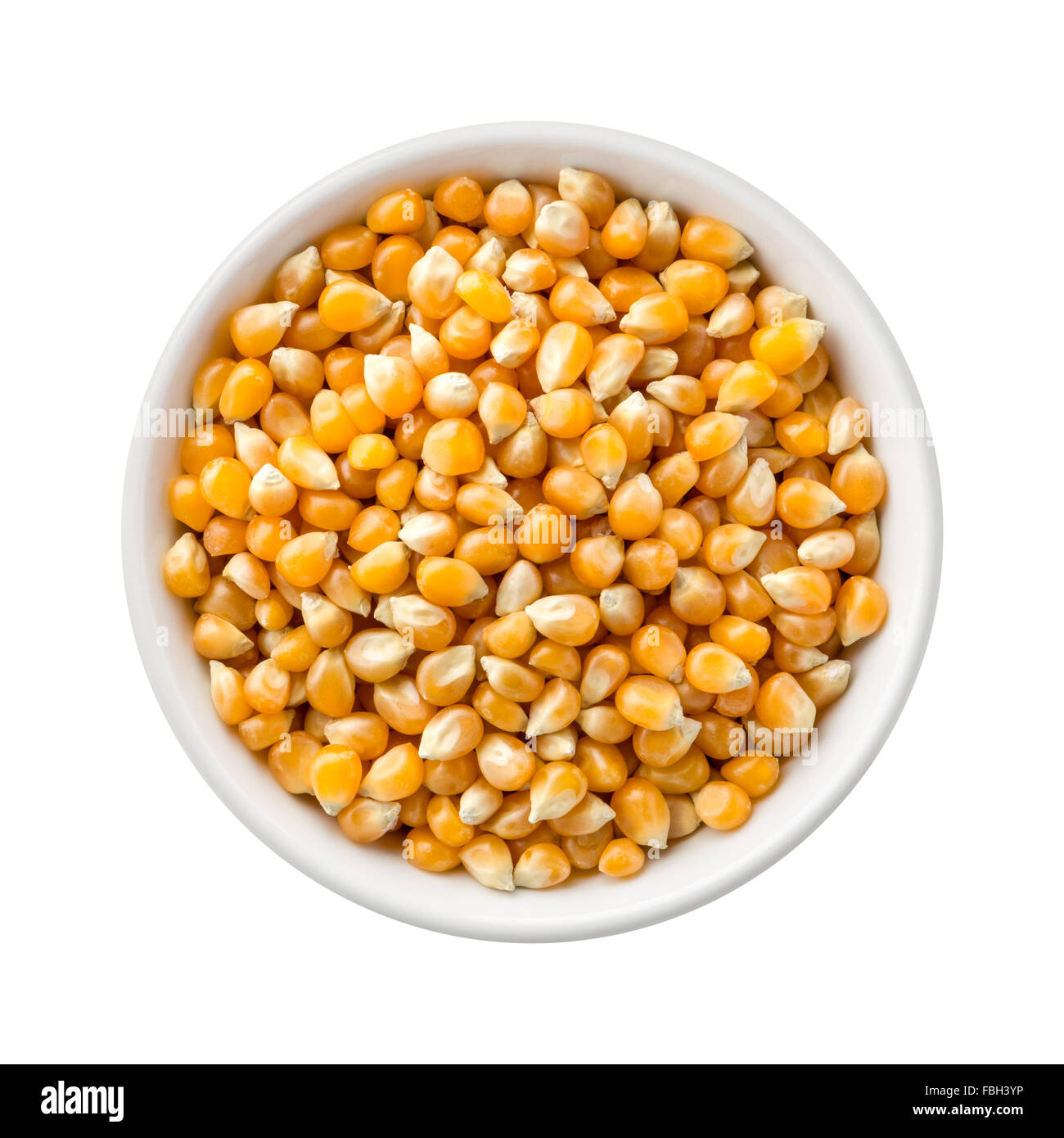 Popcorn Kernels Uncooked in a Ceramic Bowl. The image is a cut out, isolated on a white background, with a clipping - Stock Image