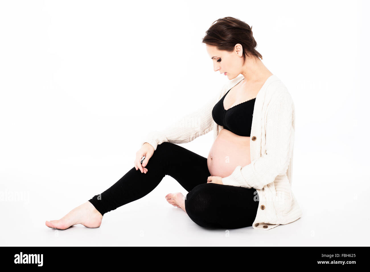 beautiful pregnant woman in black leggings and sports bra, with white wool cardigan sitting on floor, bump on show - Stock Image