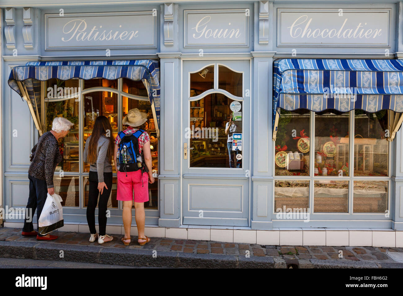 Admiring the cakes in a pâtisserie window at Mortagne-au-Perche, Normandy, France - Stock Image