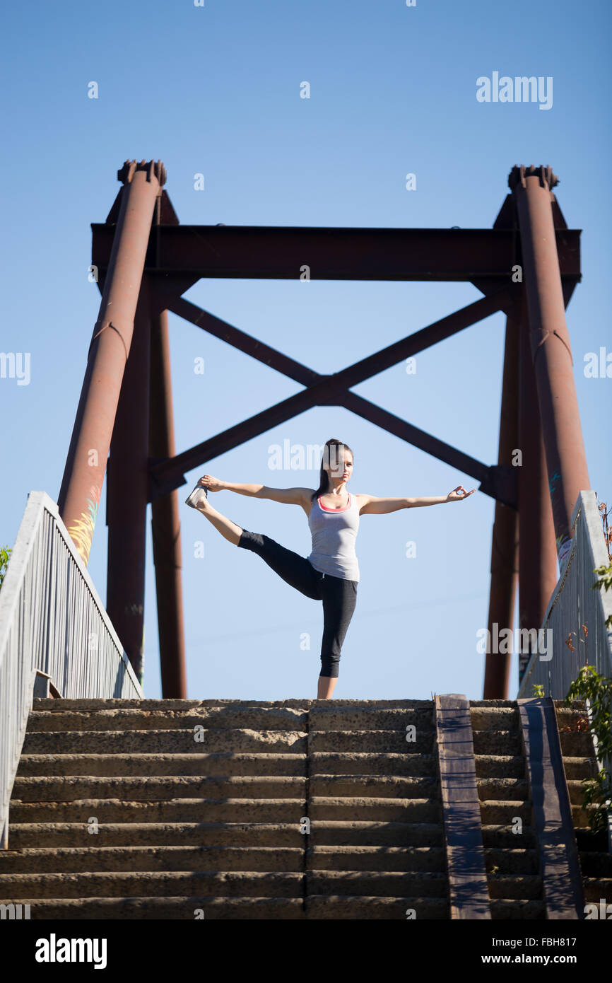 Yoga in the city: beautiful young fit woman working out on the old bridge on summer day, doing Utthita Hasta Padangustasana, - Stock Image