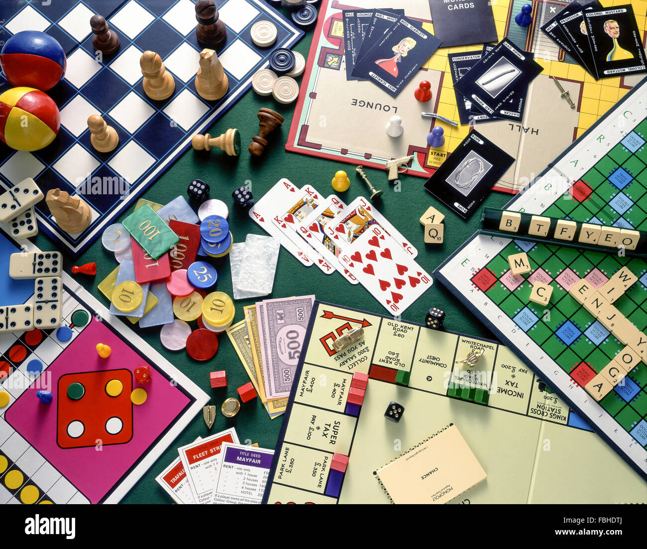 Still-life selection of board games (Monopoly, Chess, Cluedo, Scrabble) with playing cards and gambling chips - Stock Image