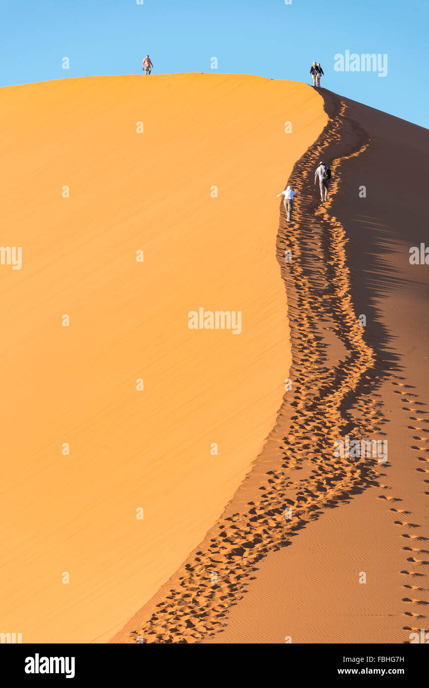 Tourist climbing sand dunes, Sossusvlei, Namib Desert, Namib-Naukluft Park, Hardap Region, Republic of Namibia - Stock Image
