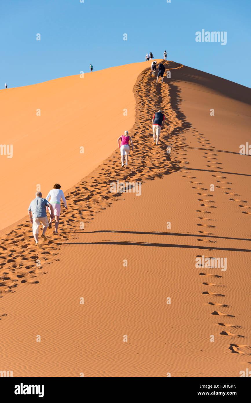 Tourists climbing sand dune, Sossusvlei, Namib Desert, Namib-Naukluft Park, Hardap Region, Republic of Namibia - Stock Image