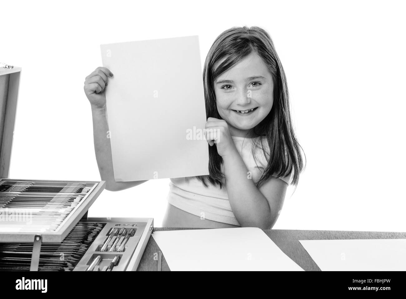 Cute girl shows her blank sheet of paper to the camera - Stock Image