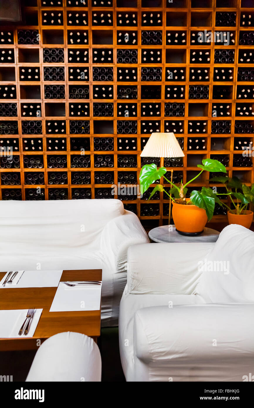 Sofas and flower vase near wine racks in a restaurant. - Stock Image