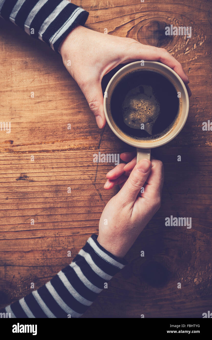 Lonely woman drinking coffee in the morning, top view of