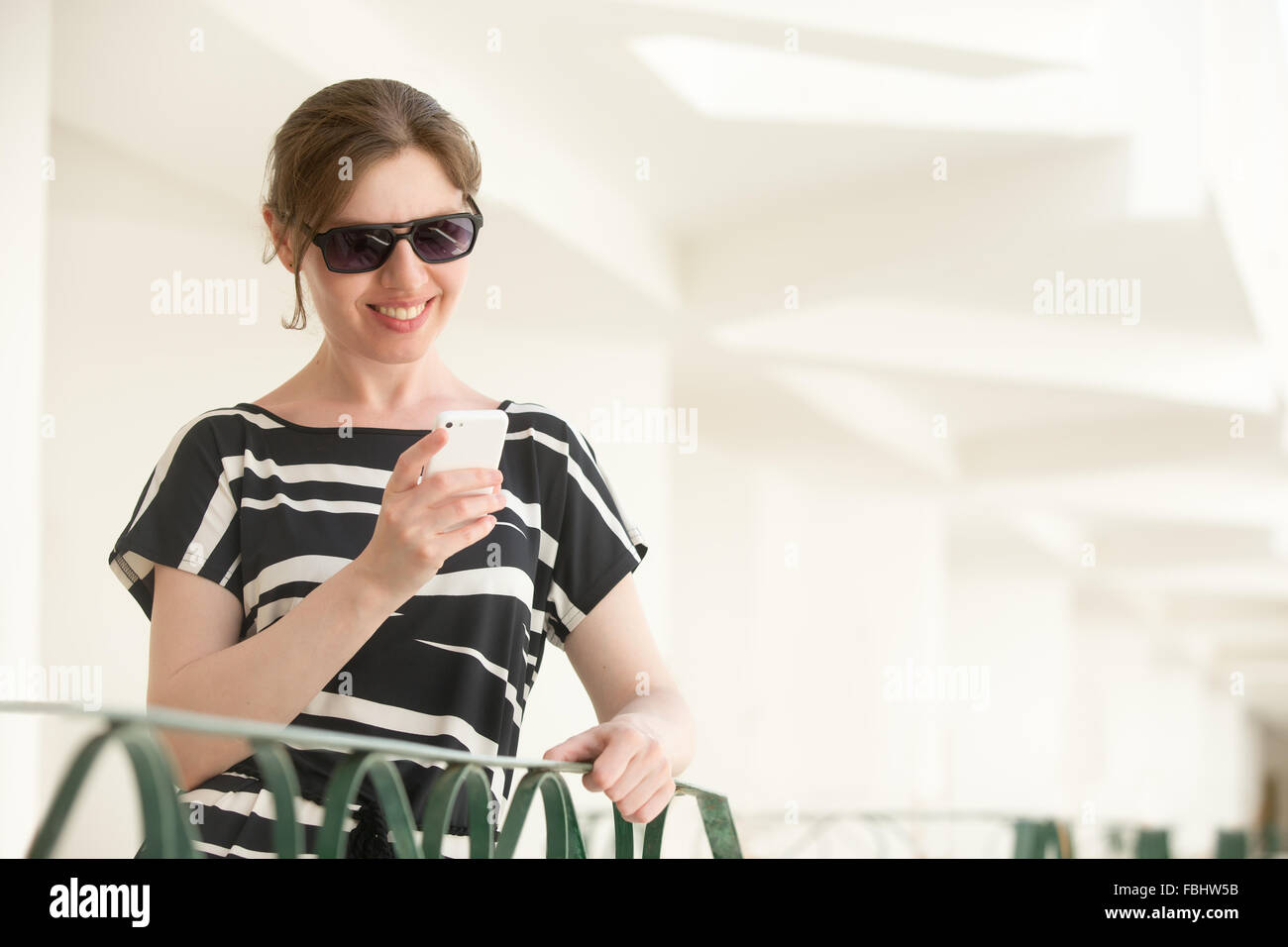 8f69075e045 Portrait of young happy smiling woman in sunglasses and black and white summer  dress standing in