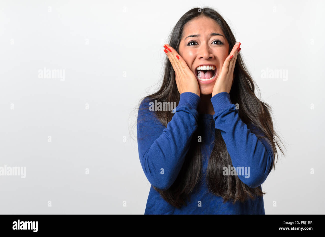 Woman reacting in terror and panic holding her hands to her cheeks as she screams , upper body on white - Stock Image