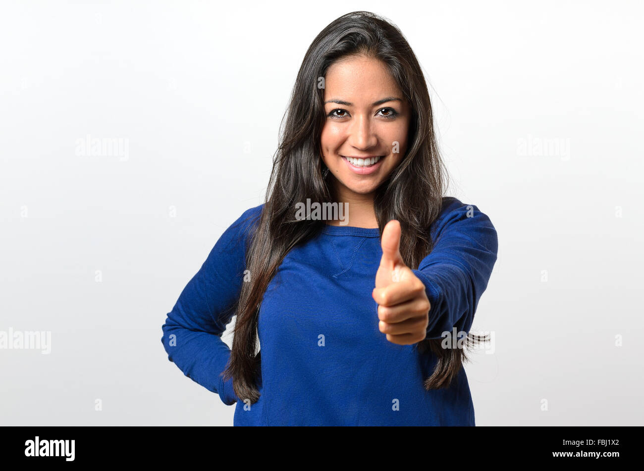 Enthusiastic motivated attractive young woman giving a thumb up gesture of approval and success with a beaming smile - Stock Image