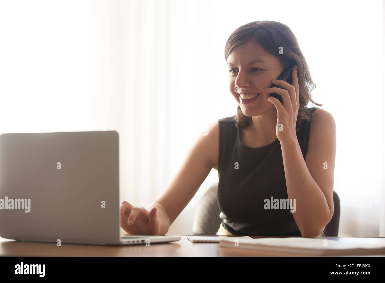 Friendly young office woman in formal wear talking on mobile phone and typing on laptop, taking orders, making business - Stock Image