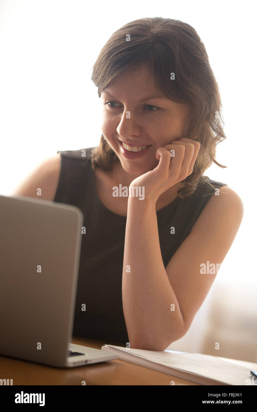 Friendly smiling young woman in formal wear using laptop, typing, working on computer, surfing internet - Stock Image