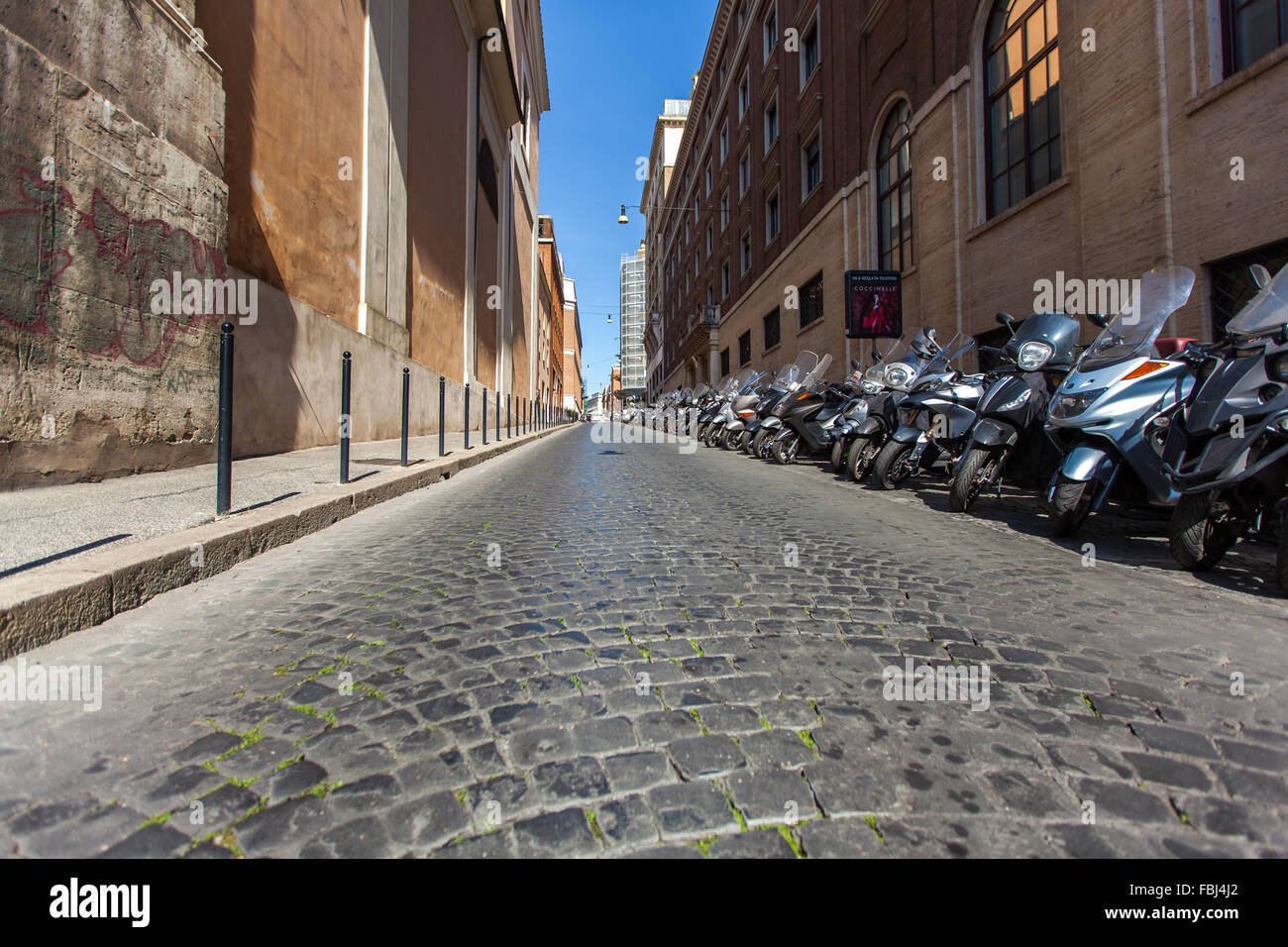 Tourism and sightseeing, narrow empty street in Rome, Italy in afternoon. Parked bikes and scooters on the roadside - Stock Image