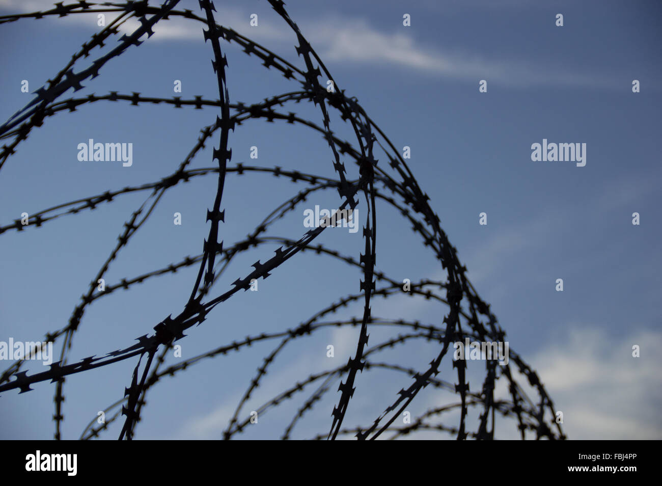 Barbed wire and sky. Just some small clouds and depressed view - Stock Image