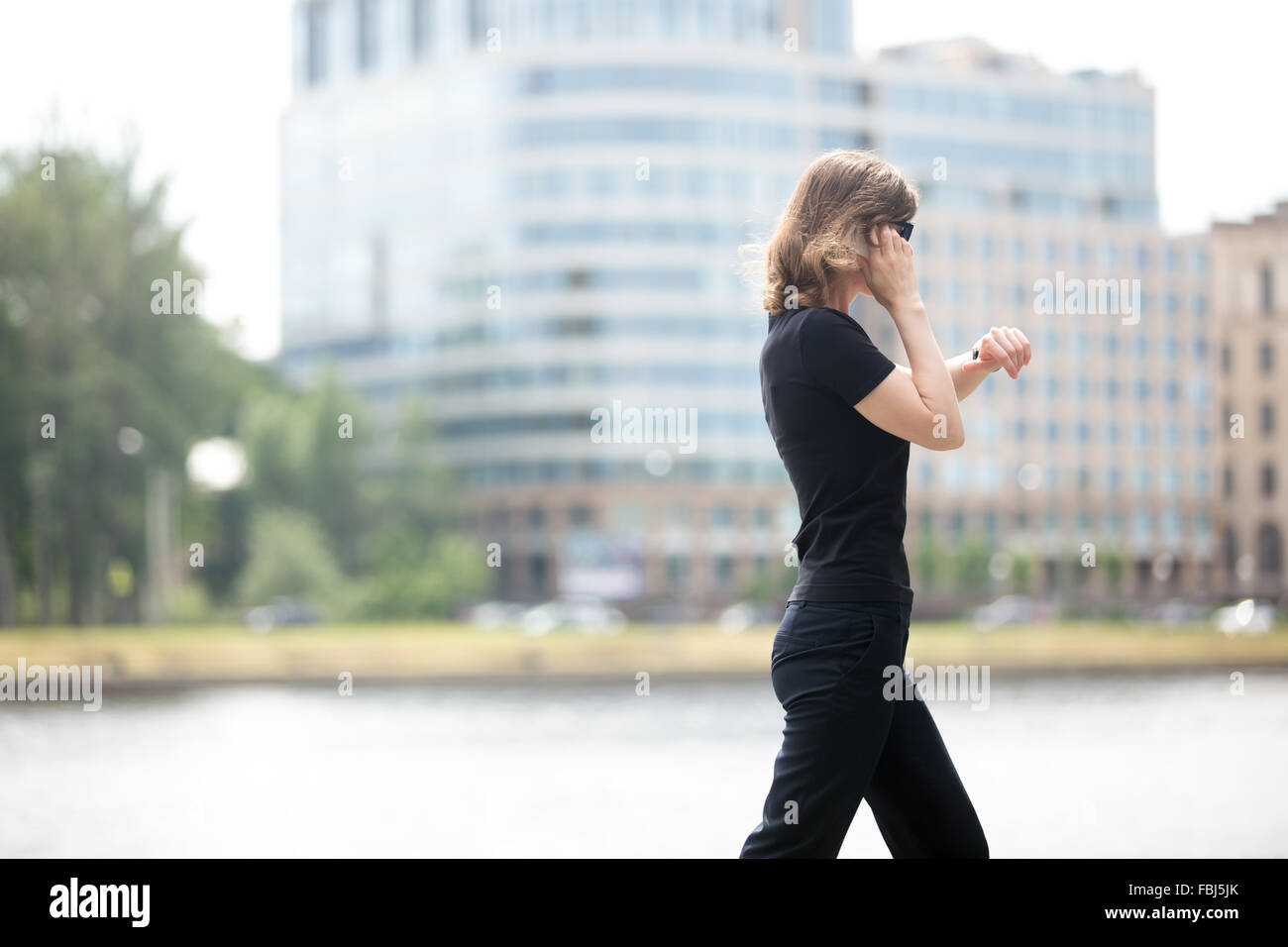 Young confident business woman walking in hurry, looking at watch, talking on mobile phone on the city street in - Stock Image