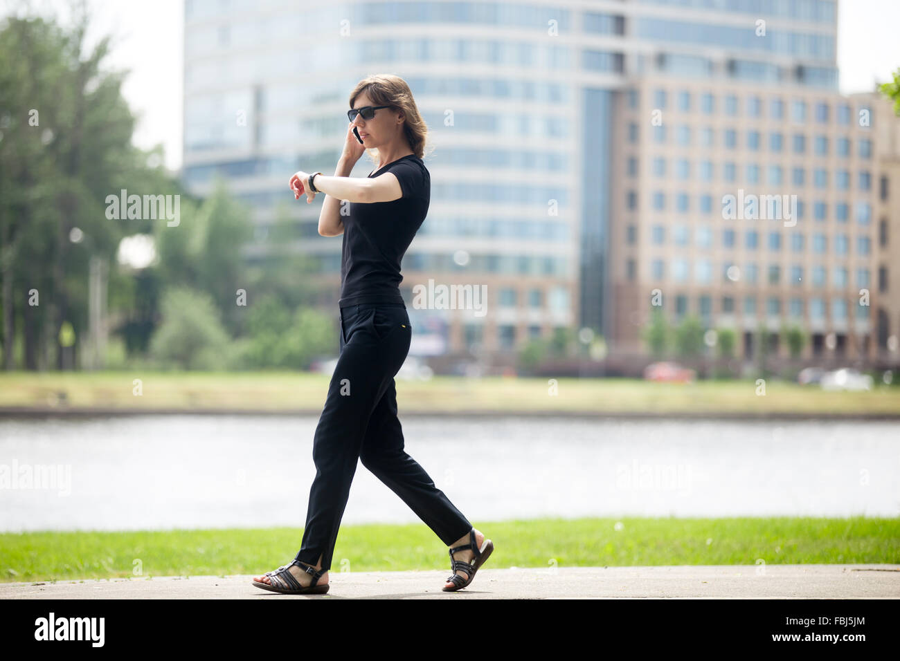 Young confident business woman walking at fast speed, looking at wristwatch, talking on cellphone on the city street - Stock Image