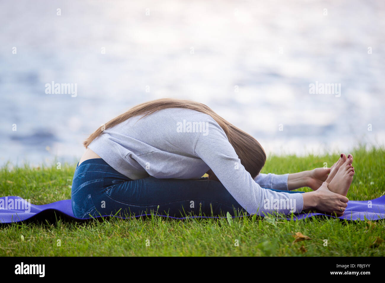 Beautiful sporty young woman working out on street on blue mat, doing stretching exercises on riverbank in park, - Stock Image