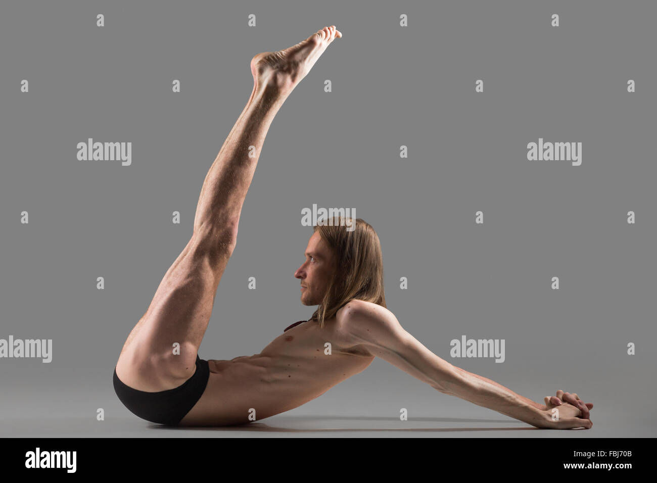 Sporty muscular young yogi man doing exercises for abdominal muscles and shoulders, lifting up legs, studio shot - Stock Image