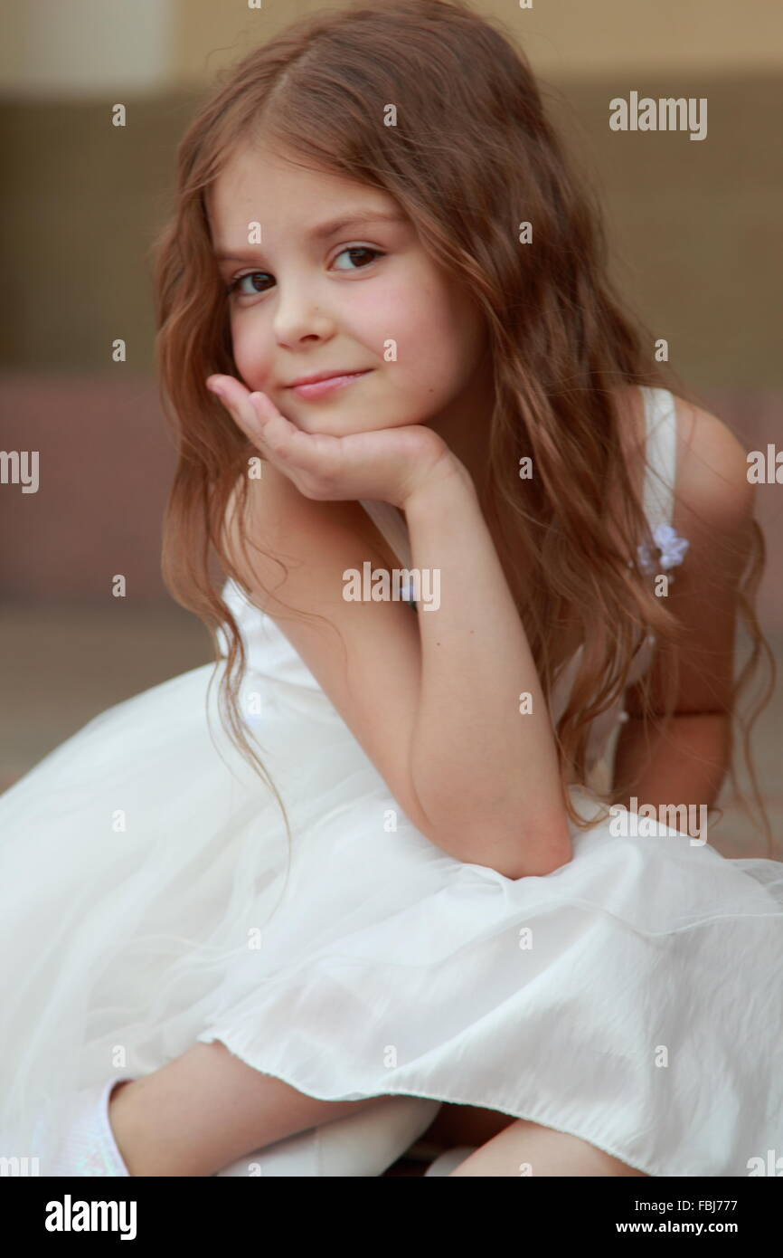 Portrait Of Cute Smiling Little Girl With Long Hair In A Beautiful