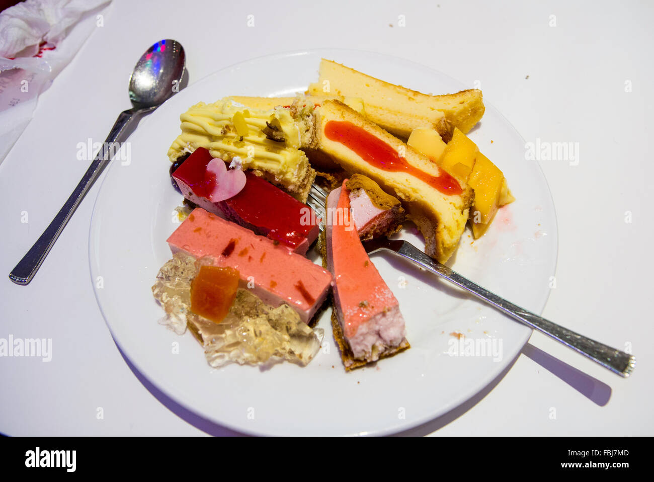 Japan. 'Sweet Paradise' Japanese famous all-you-can-eat cake and sweet restaurant. Plate, with folk, full - Stock Image