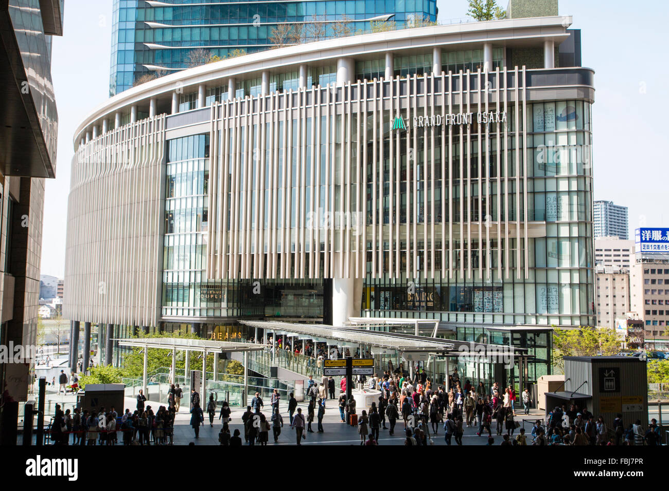 'Grand Front Osaka' store, in Umeda, Osaka. Modern glass metal framed multi story building with crowded - Stock Image