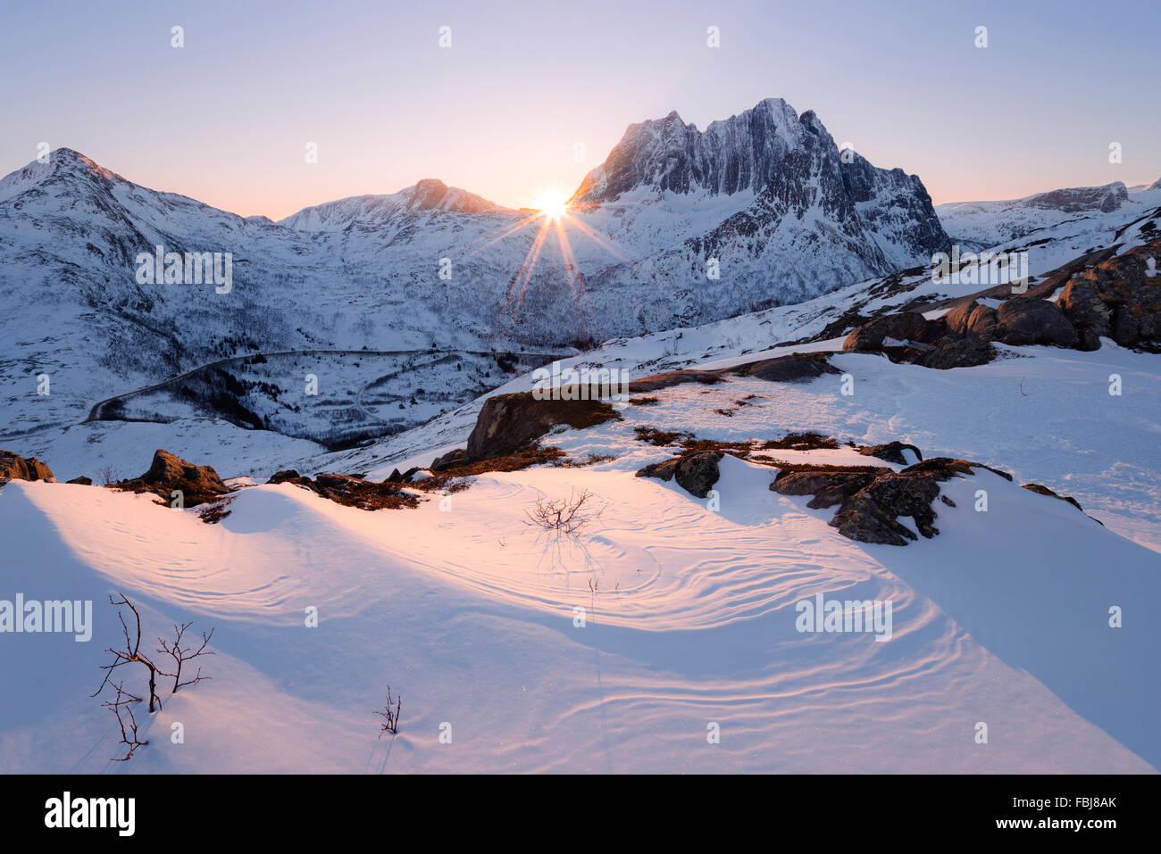 Norway, Nordland, Senja, island, mountain, back light, sun, star, rays, light, curved, snow, winter, soft, bizarre, - Stock Image