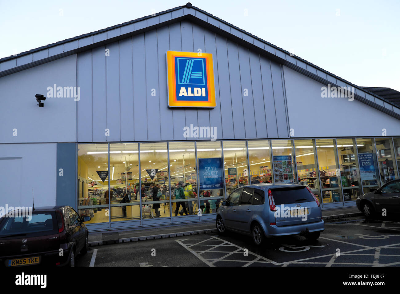Exterior evening view looking through windows at customers in Aldi Supermarket sign and logo Wales UK   KATHY DEWITT - Stock Image
