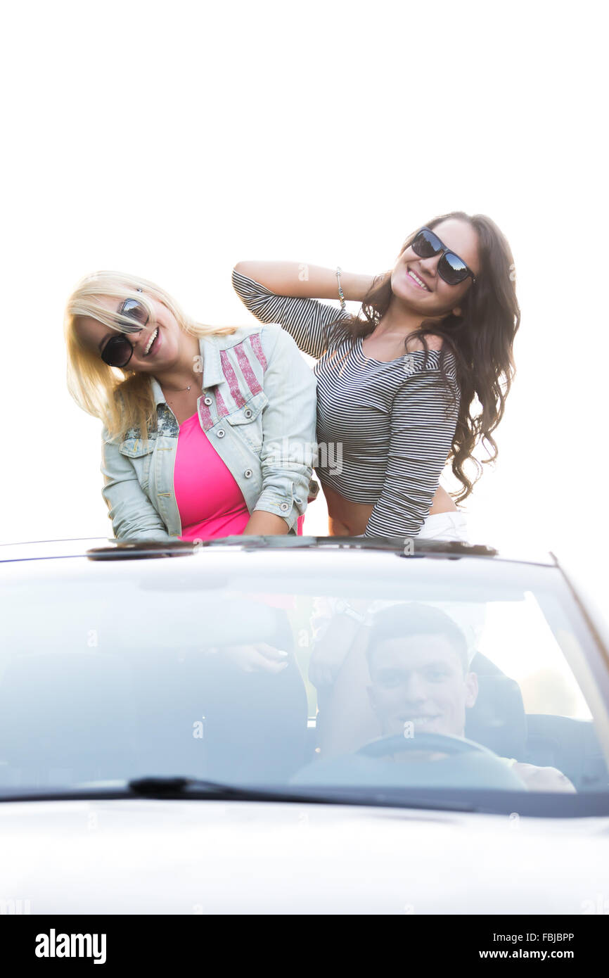 Group of three carefree smiling friends going on vacation, traveling together in cabriolet on summer day, girls - Stock Image