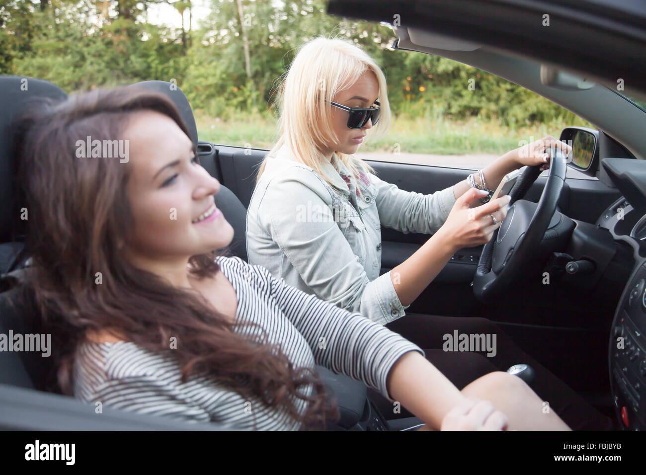 Two Beautiful Traveler Young Women Friends Riding Black Sports Car