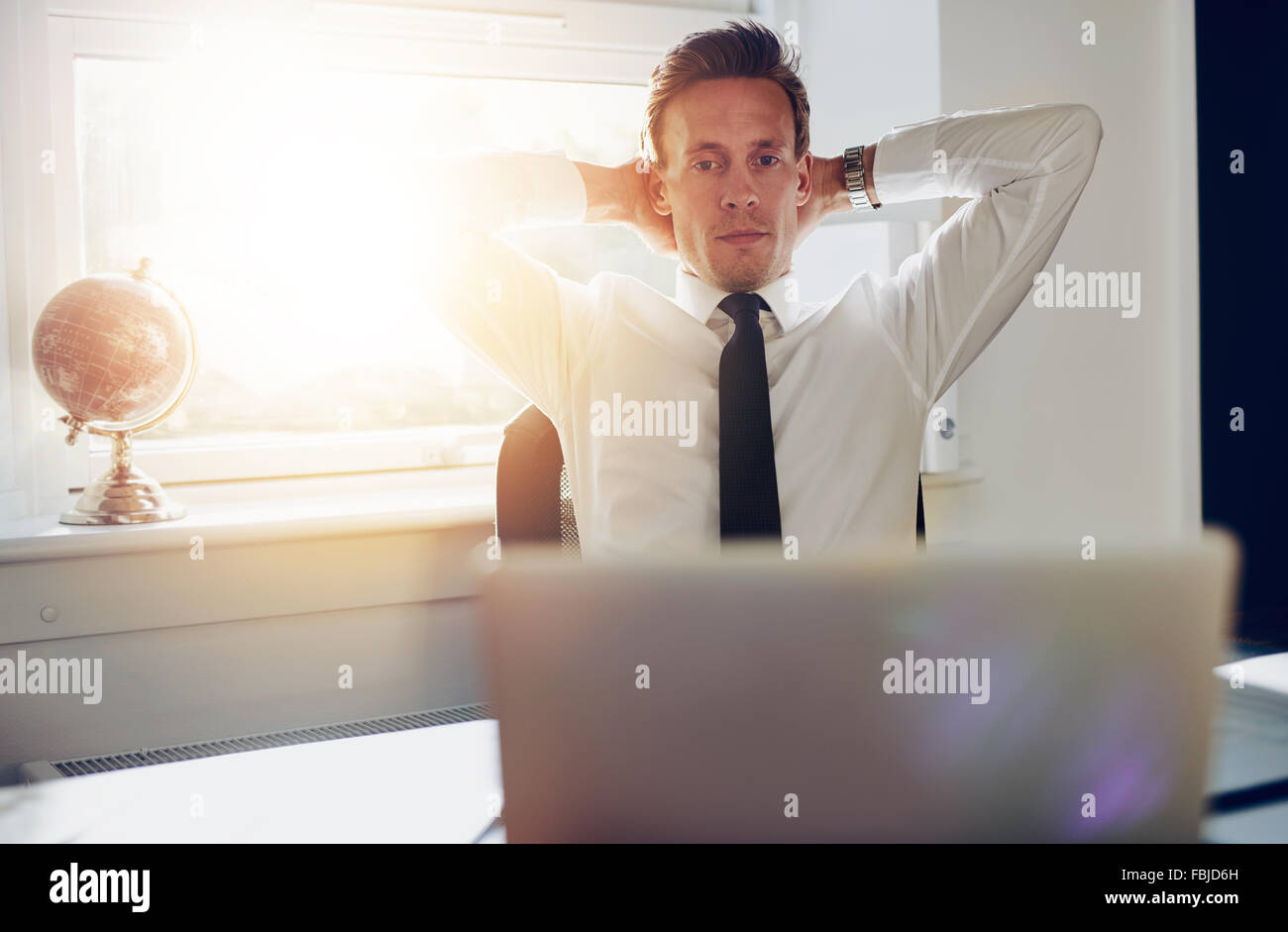 White male executive working overtime at office, looking at his laptop while leaning back on his chair - Stock Image
