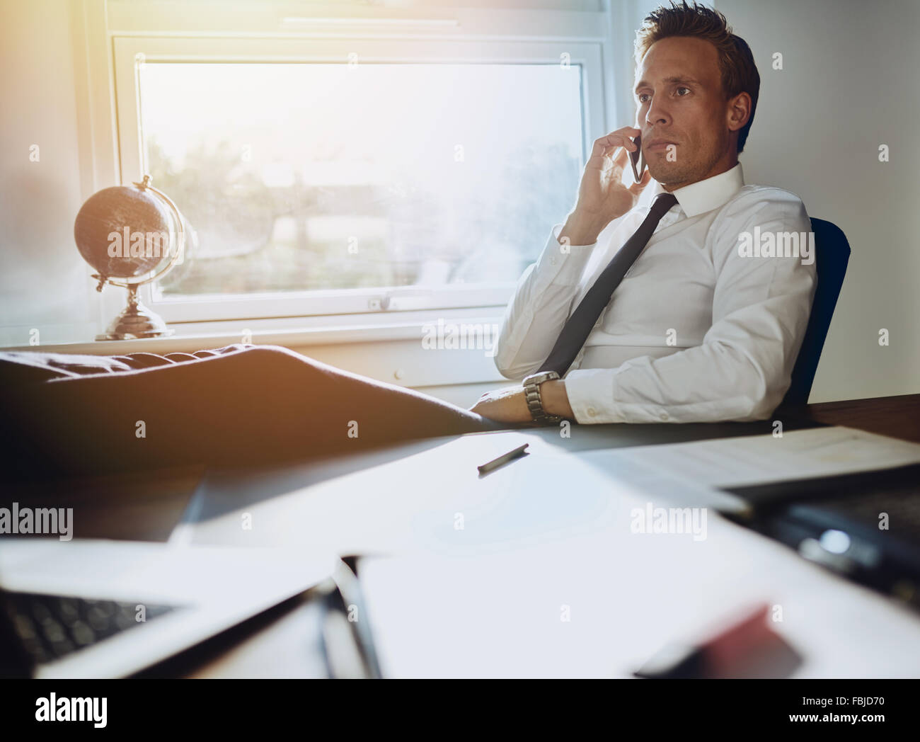 Laid back confident business man sitting at his desk with feet up talking on phone with documents on his desk Stock Photo
