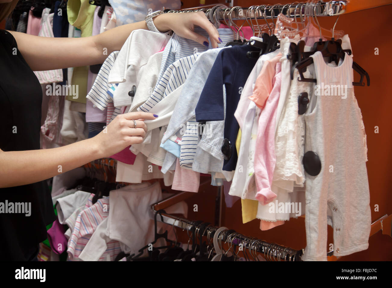 Young beautiful woman shopping, standing in department store in front of rack with baby clothes, looking for new - Stock Image