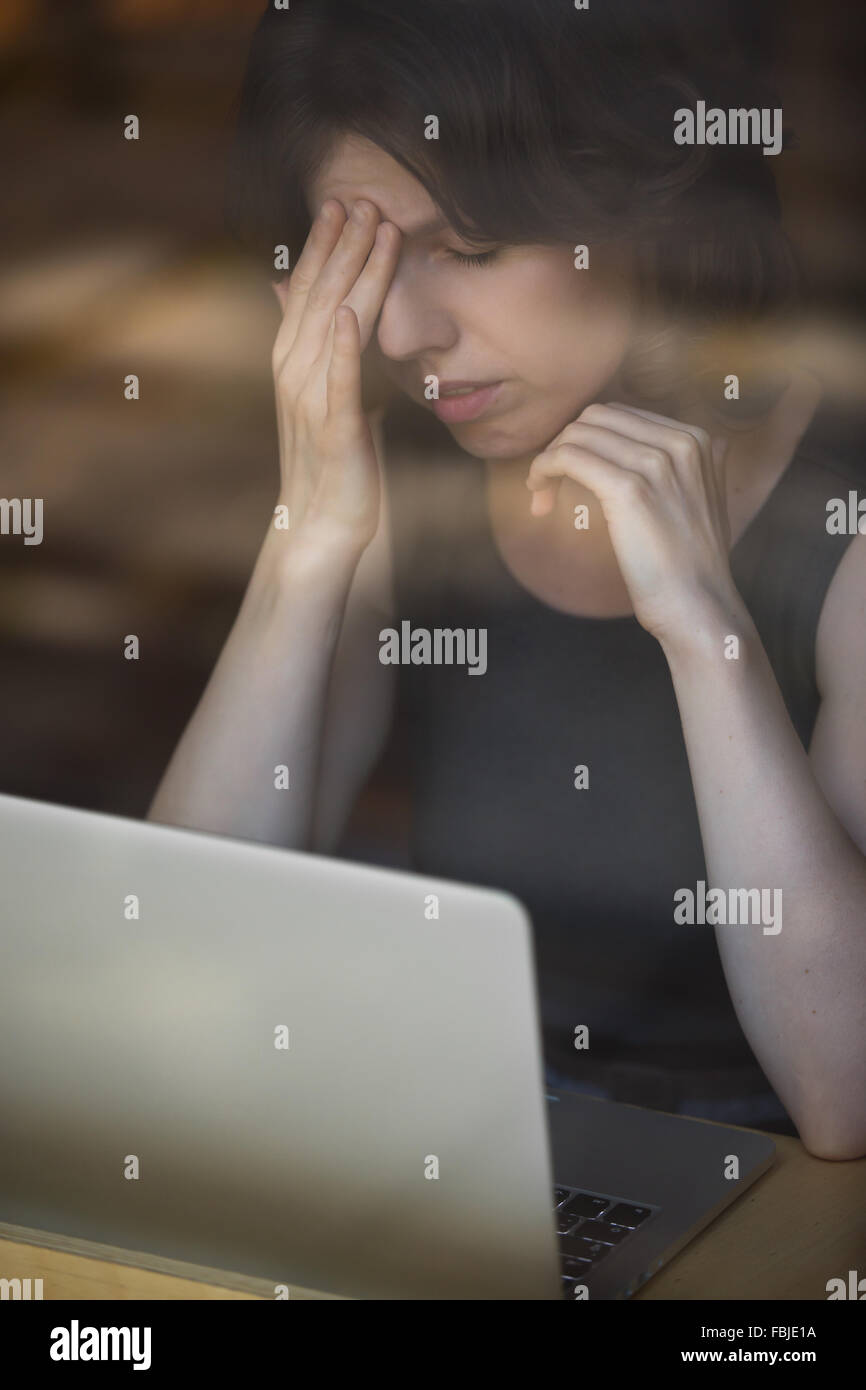 Young woman sitting in cafe in front of laptop, leaning on her hand, touching head with tired expression, having - Stock Image