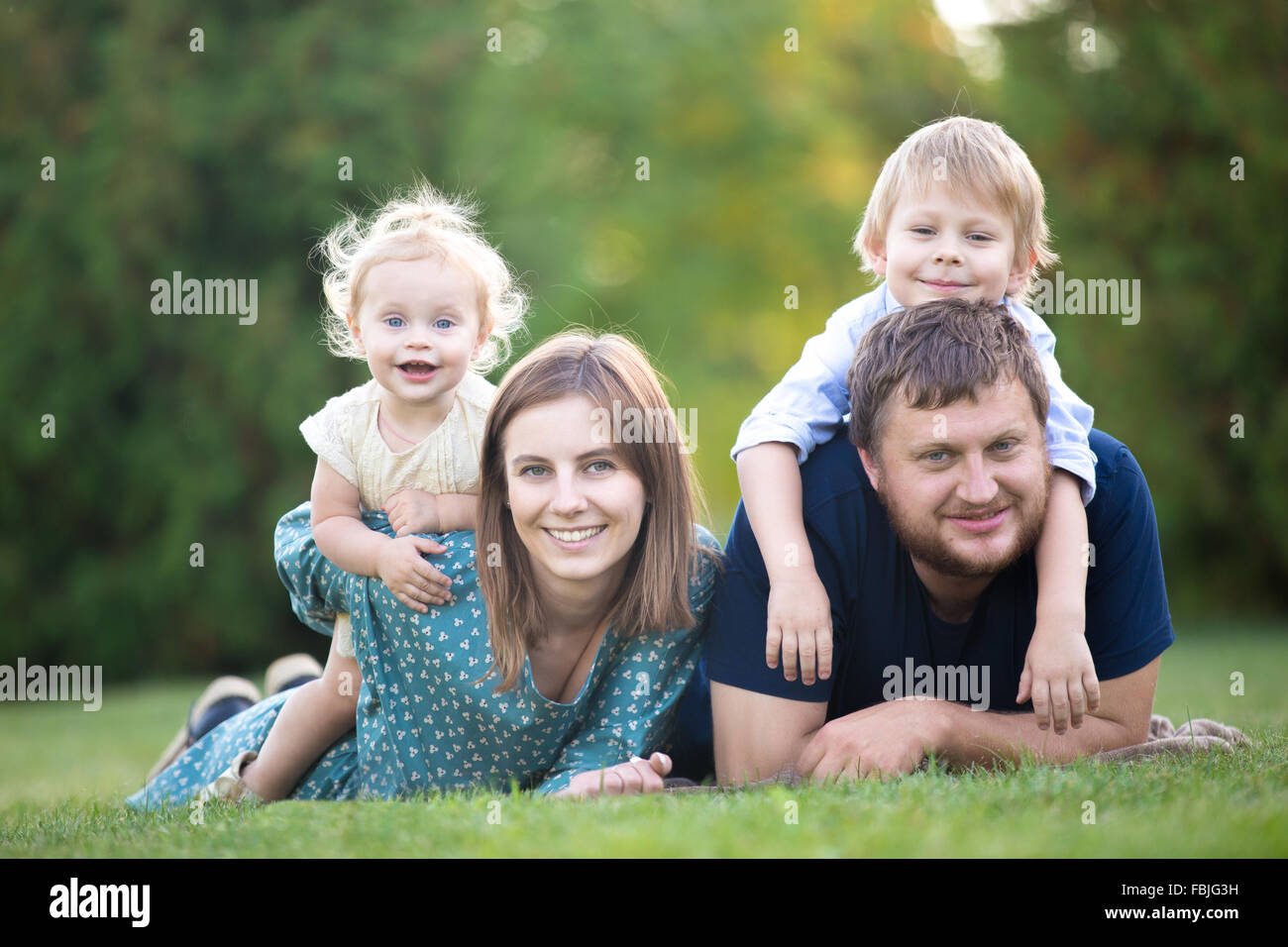 Mother, father and two kids lying on grass in park. Portrait of happy beautiful family of four relaxing on meadow, Stock Photo