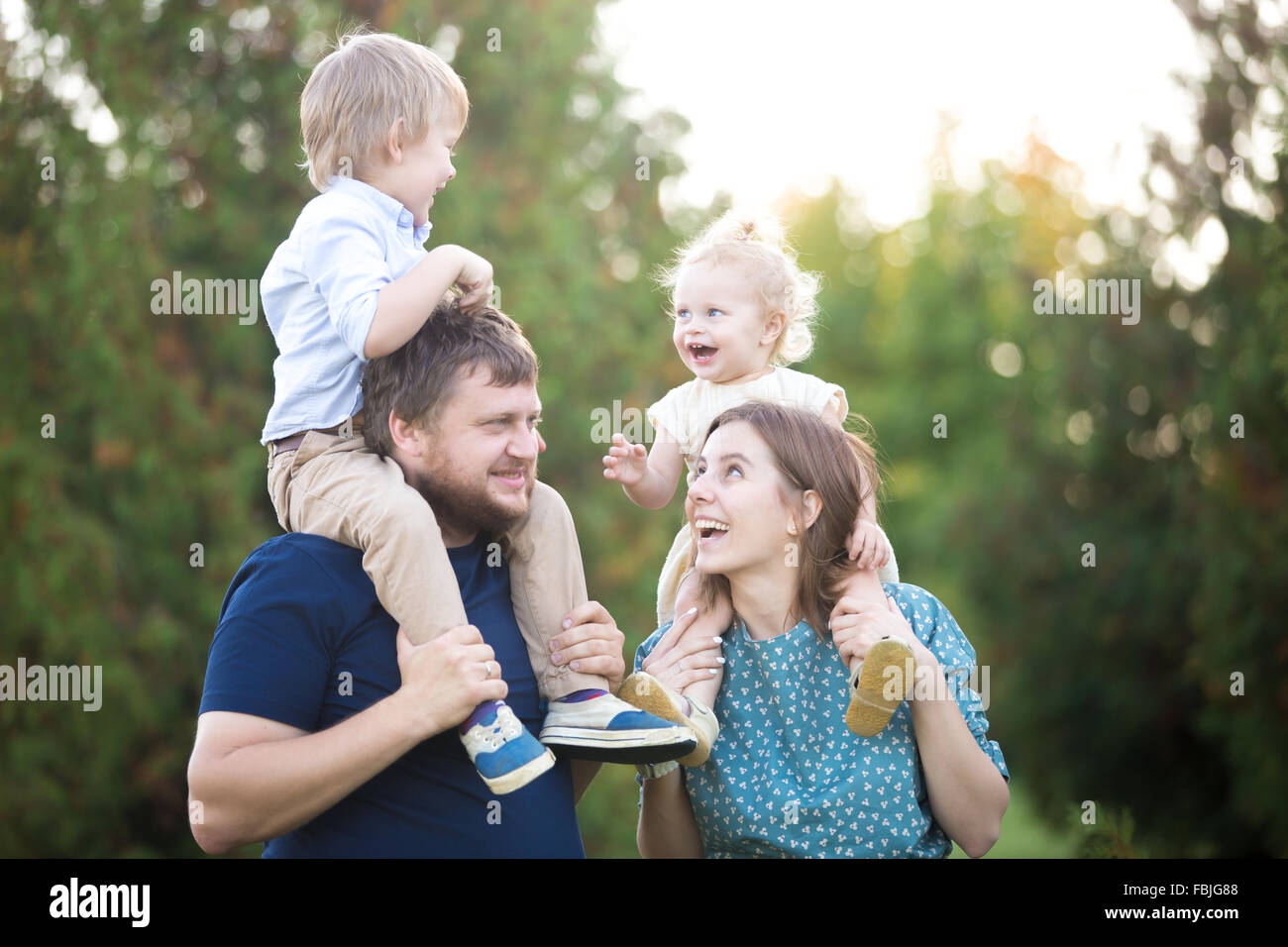 Portrait of happy beautiful family of four walking in park in summer. Mom and dad carrying two little cheerful laughing - Stock Image