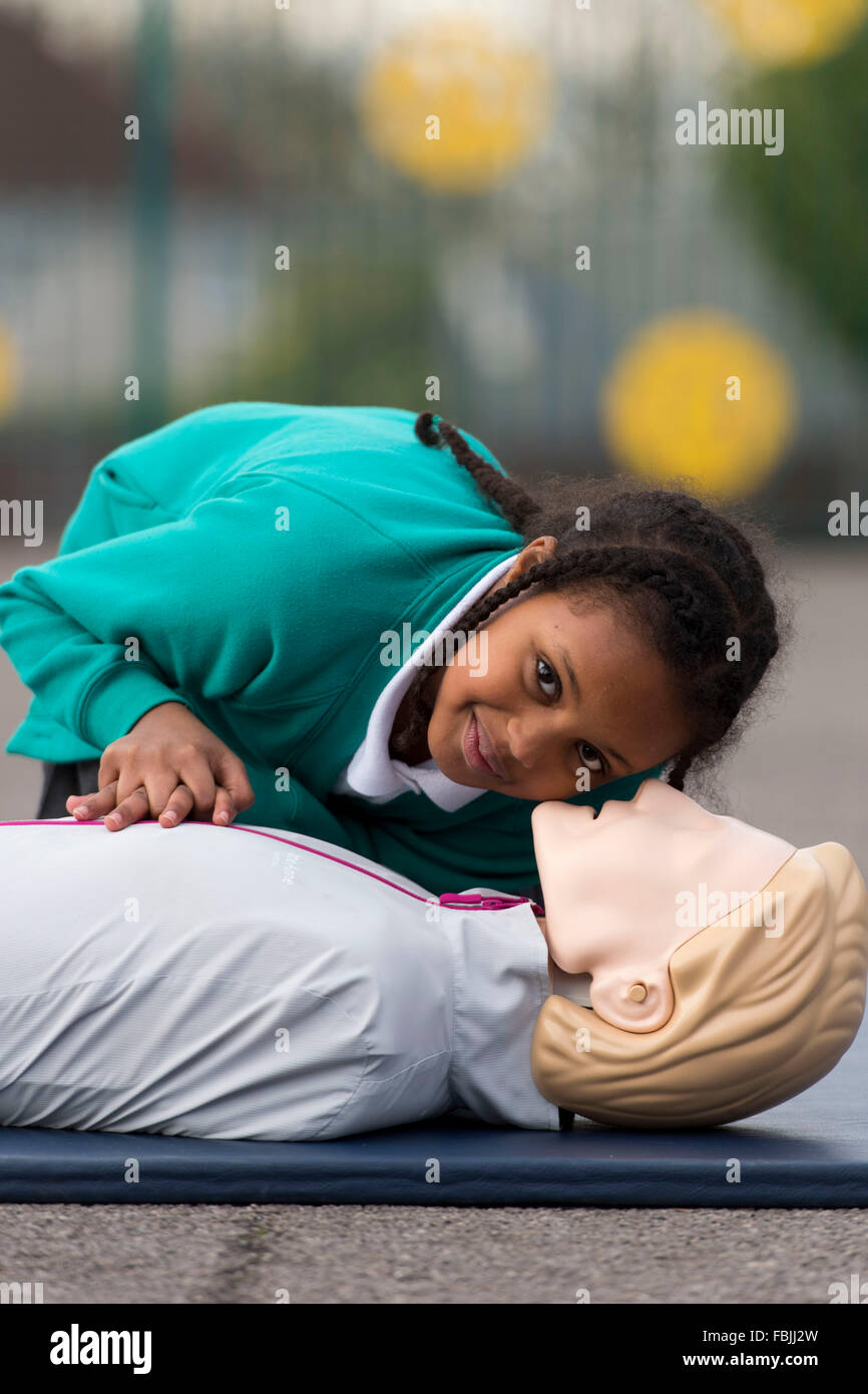 A schoolgirl learns life saving first aid techniques by practicing on a dummy at school. - Stock Image