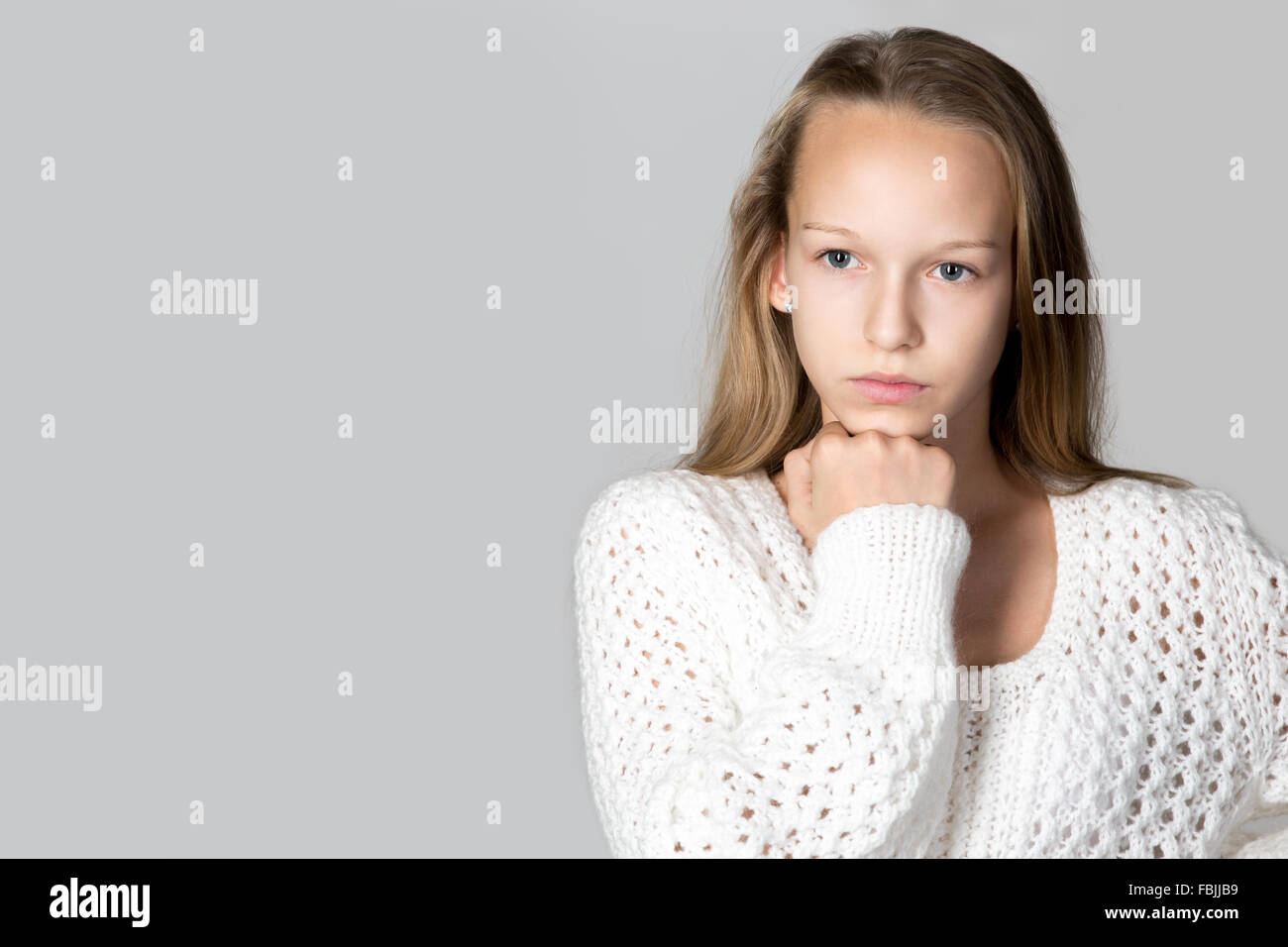Portrait of beautiful focused pensive casual caucasian teenage girl wearing white knitted sweater, studio image, Stock Photo