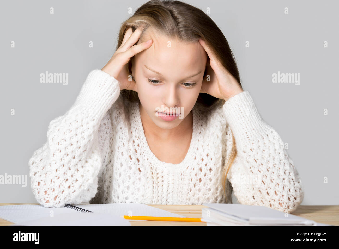 Portrait of unhappy beautiful casual girl, sitting at desk, holding her head in arms with overwhelmed frustrated - Stock Image