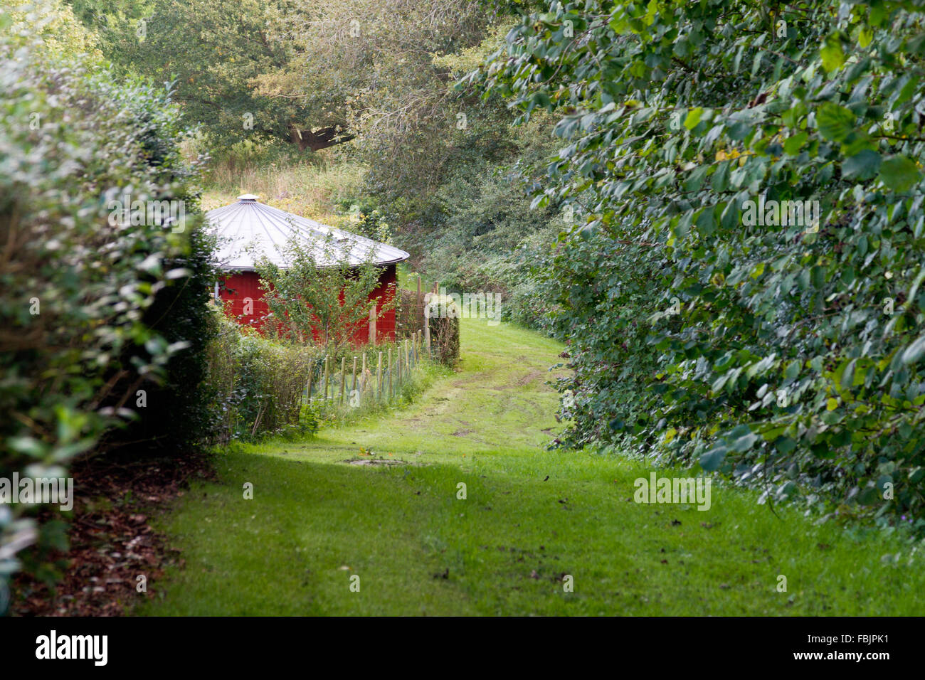 Round building with red walls alongside a country path through lush countryside in Grasten, Denmark. - Stock Image