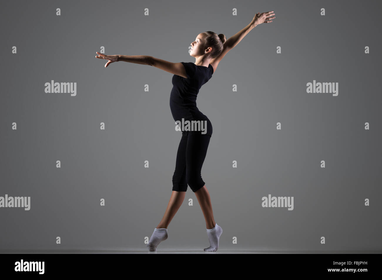 Beautiful cool young fit gymnast athlete woman in sportswear working out, dancing on tiptoes, doing art gymnastics - Stock Image