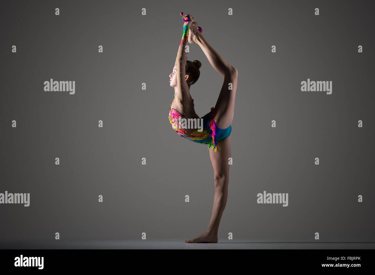 Beautiful cool young fit gymnast woman in colorful sportswear working out, standing on one leg, performing back - Stock Image