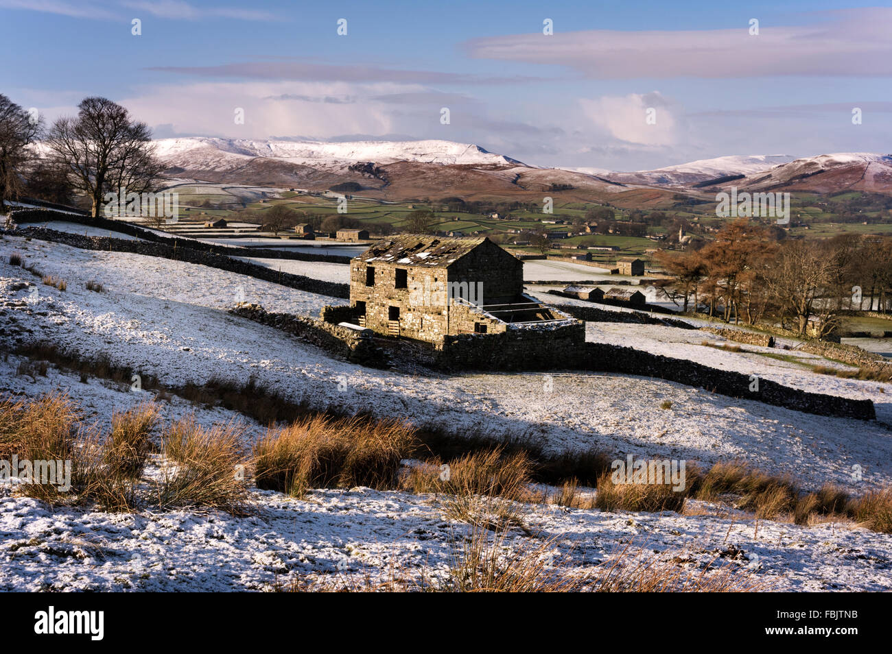 Traditional Yorkshire Dales barns with the market town of Hawes and a snow-covered Widdale Fell beyond, North Yorkshire, - Stock Image
